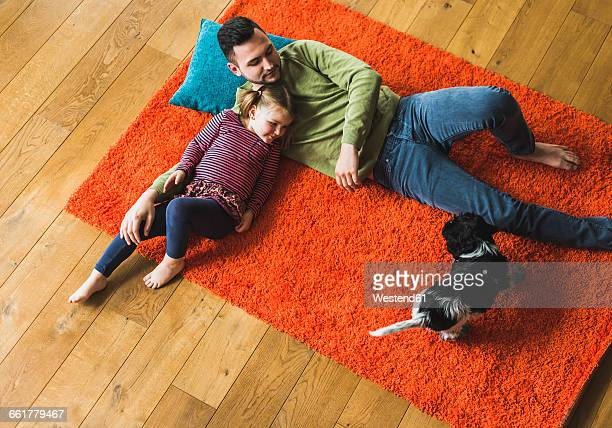 Father and daughter lying on carpet on the floor with dog