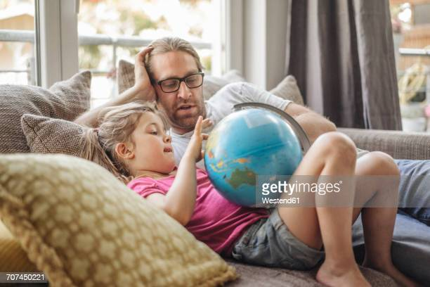 father and daughter lying with globe on sofa - world kindness day fotografías e imágenes de stock