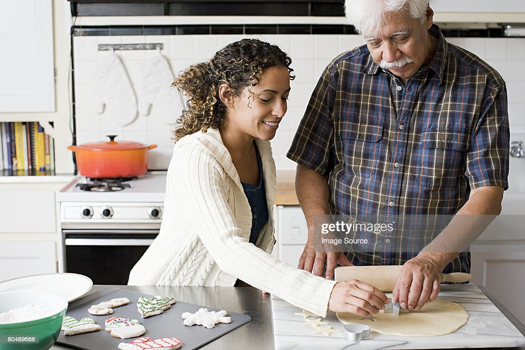 A father and daughter making cookies : Stock Photo