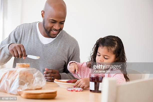 Father and daughter making sandwiches