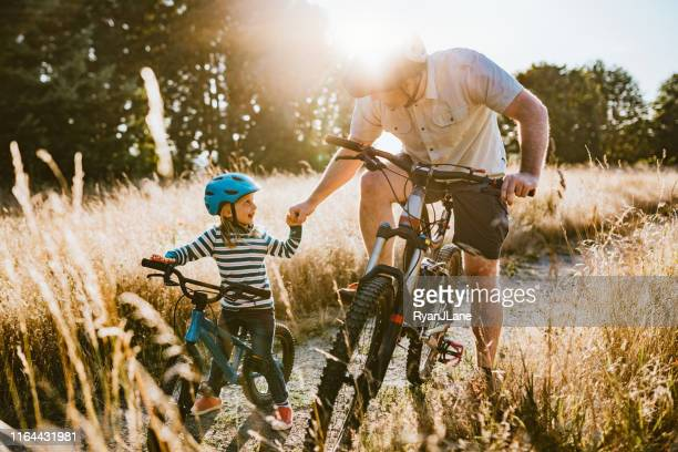 father and daughter mountain bike riding together on sunny day - leisure equipment stock pictures, royalty-free photos & images