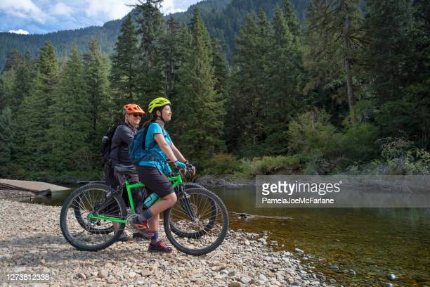 father and daughter mountain bikers enjoying view from riverbank - vancouver canada stock pictures, royalty-free photos & images