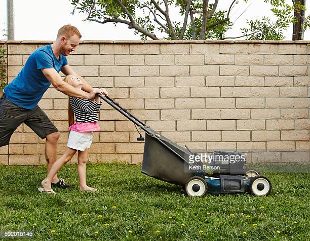 Father and daughter mowing lawn in backyard