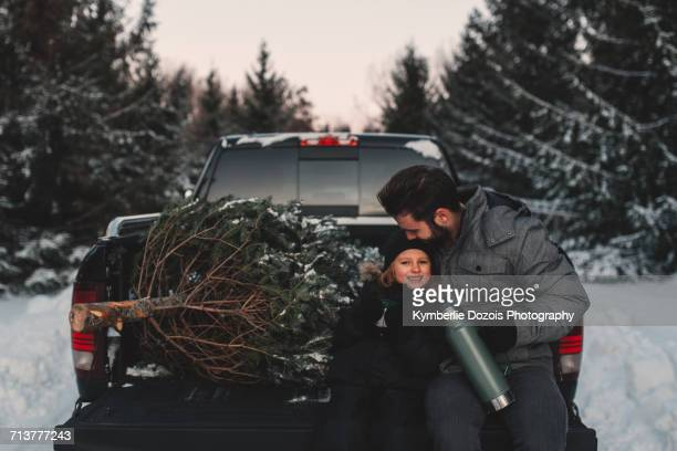 Father and daughter on back of pick up truck with their Christmas tree