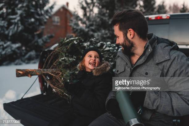 father and daughter on back of pick up truck with their christmas tree - peterborough ontario stock photos and pictures