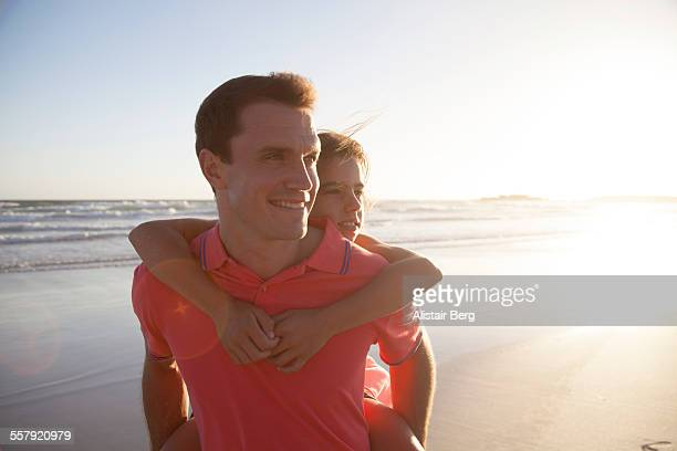 Father and daughter on beach at sunset