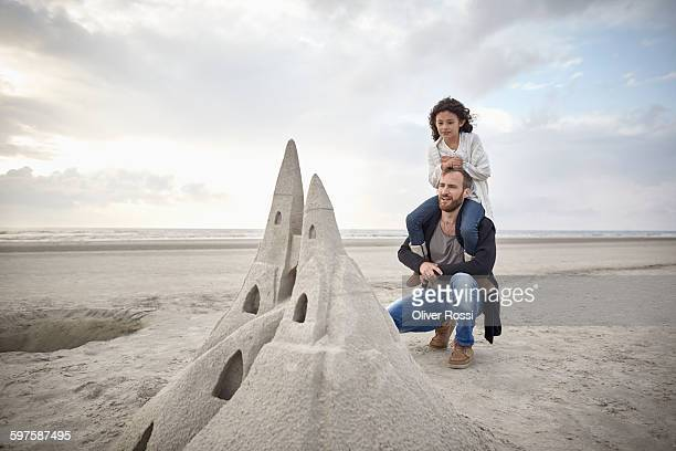 Father and daughter on beach looking at sandcastle