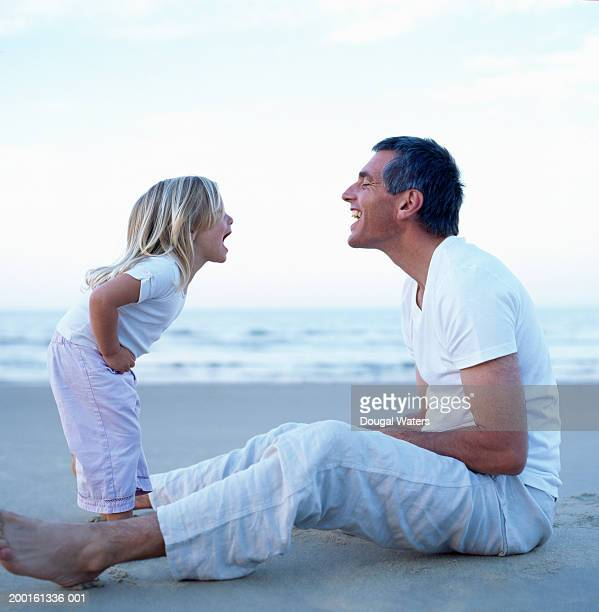 Father and daughter (2-4) on beach screaming at one another, profile