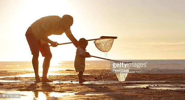 Father and daughter on beach with nets
