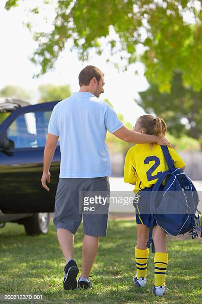 Father and daughter (9-11) on field, girl in soccer uniform, rear view