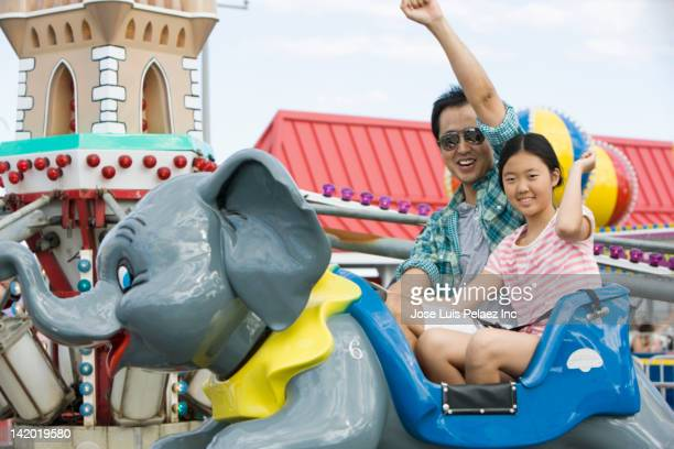 Father and daughter on ride at amusement park
