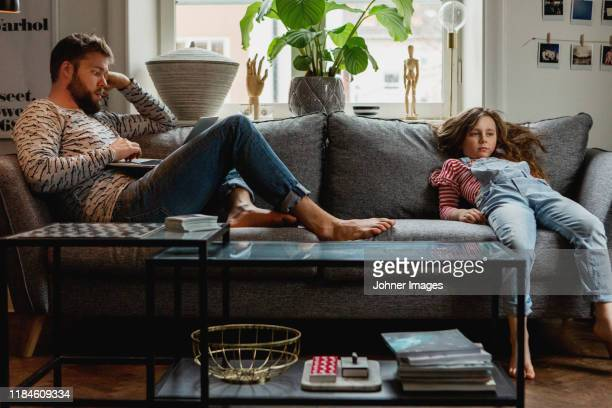 father and daughter on sofa - boredom stock pictures, royalty-free photos & images
