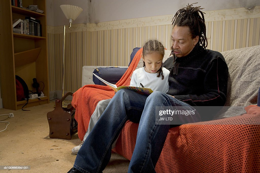 Father and daughter on sofa with book : Stock Photo