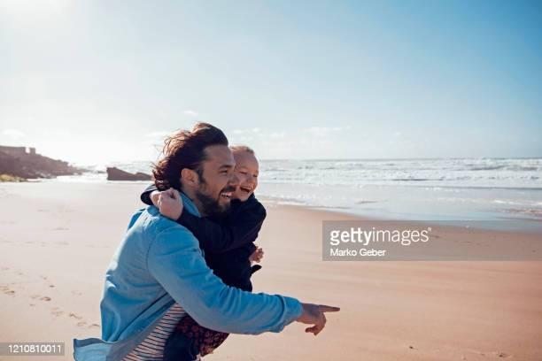 father and daughter on the beach - travel stock-fotos und bilder