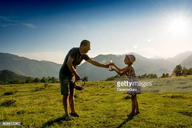 padre e hija en el prado de montaña, parando para tomar un refresco de agua - dan peak fotografías e imágenes de stock