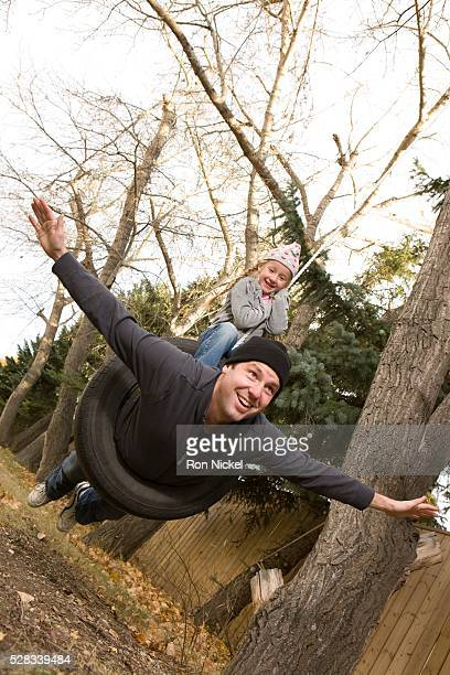 father and daughter on tire swing - crazy dad stock photos and pictures