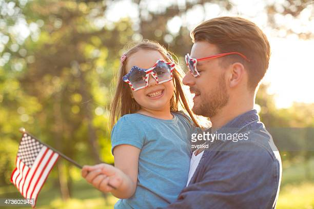 father and daughter outdoors in a meadow on july 4th. - independence day stock pictures, royalty-free photos & images