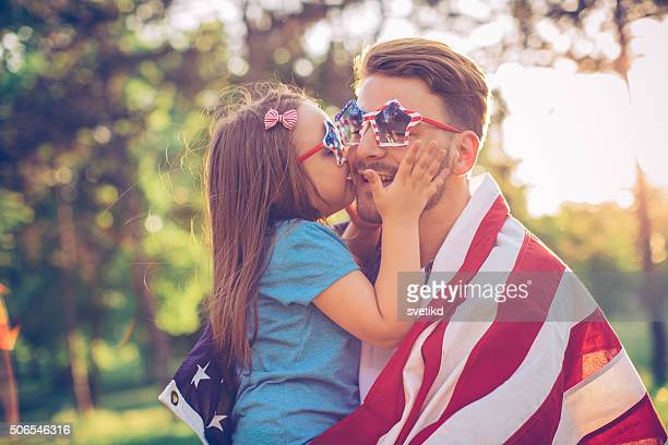 Father and daughter outdoors in a meadow on july 4th.