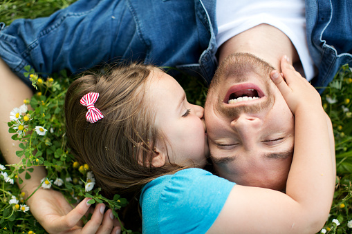 Father and daughter outdoors in a meadow. 473247804