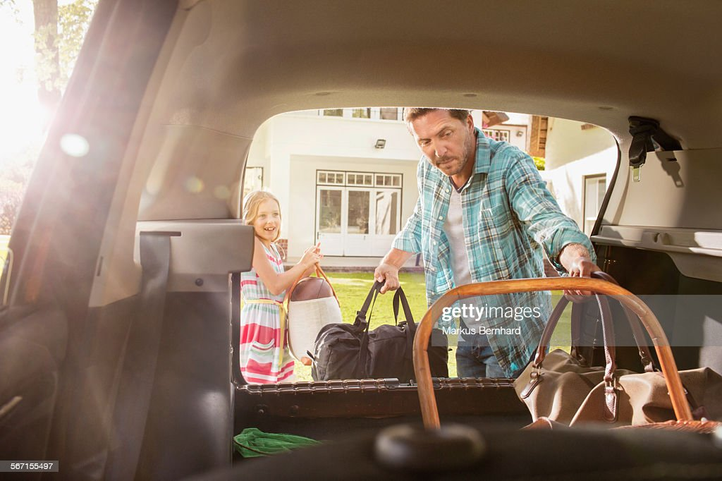Father and daughter packing car. : Stock Photo