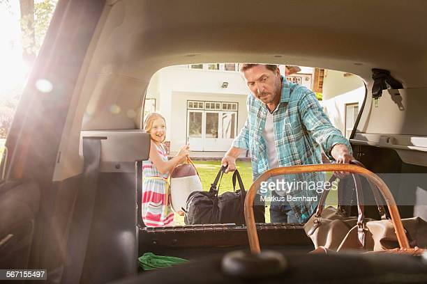 Father and daughter packing car.