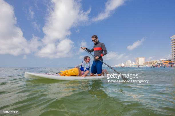 father and daughter paddle boarding in the gulf of mexico, florida, usa - destin beach stock pictures, royalty-free photos & images