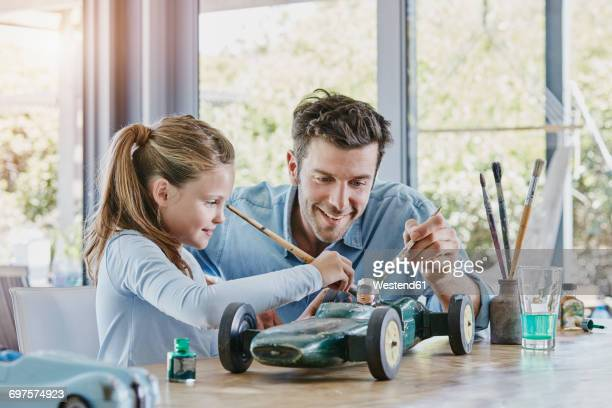 Father and daughter painting a toy race car