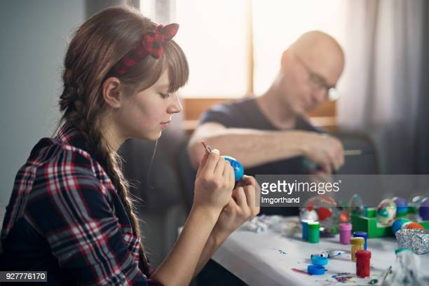 Father and daughter painting Easter eggs