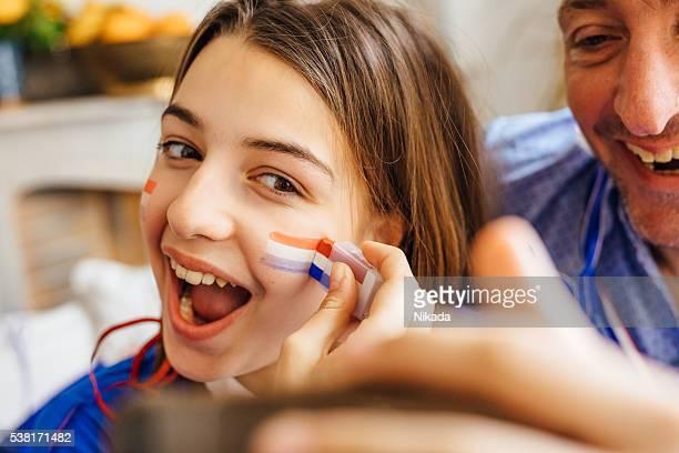 Père et fille avec peinture visage tricolore et prenant un selfie