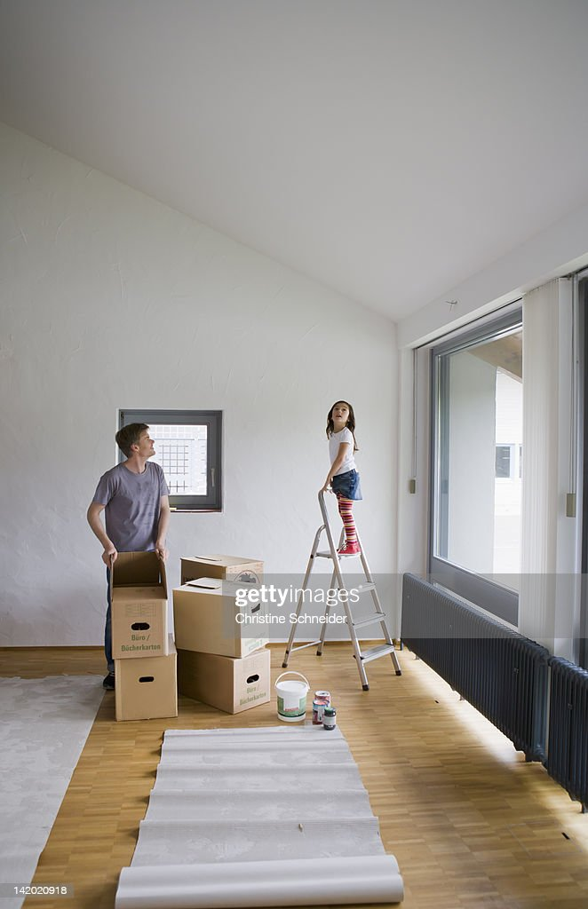 Father and daughter painting new house : Stock Photo