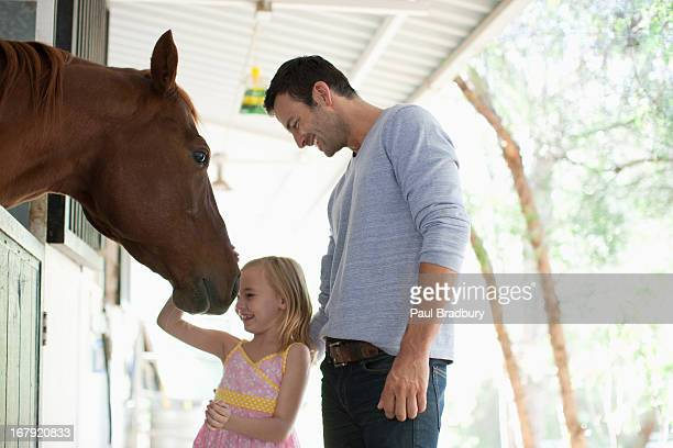 Father and daughter petting horse