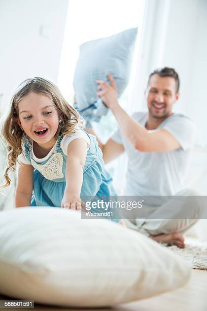 Father and daughter pillow fighting
