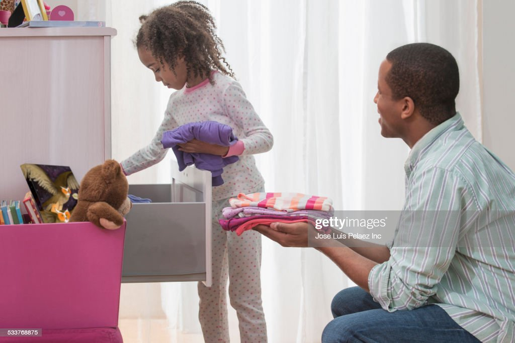Father and daughter placing laundry in drawers : Foto stock