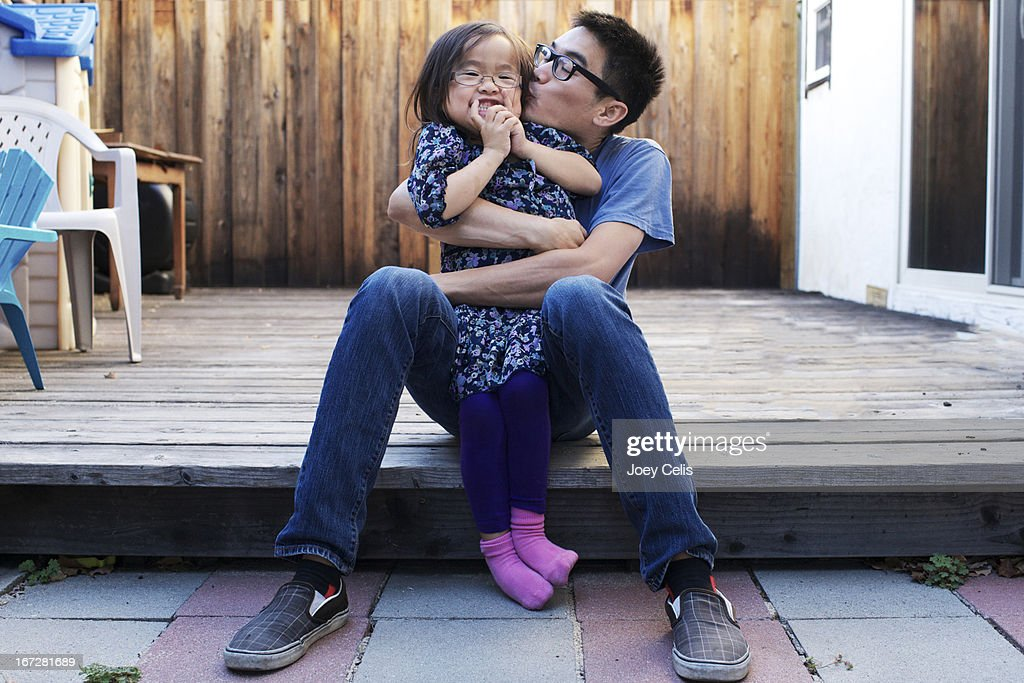Father and daughter playfully hug and kiss : Stock Photo