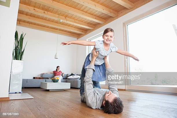 Father and daughter playing at home, pretending to fly
