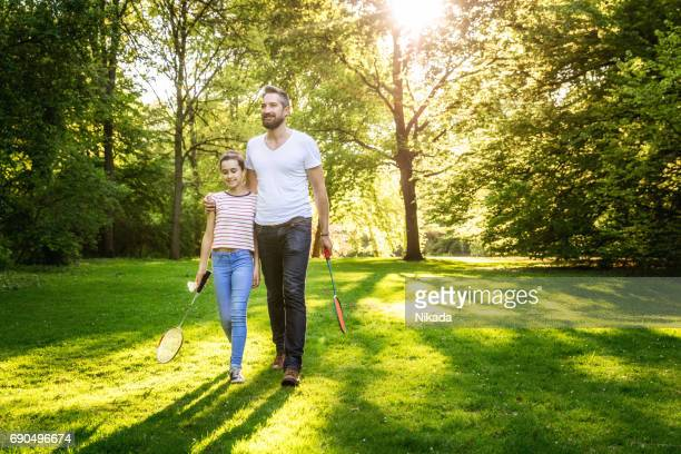 father and daughter playing badminton in the park