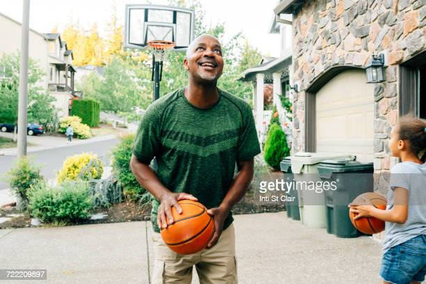 father and daughter playing basketball in driveway - african american family home stock photos and pictures