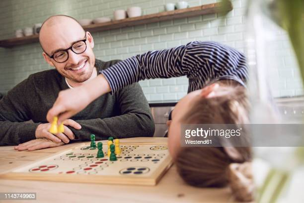 father and daughter playing board game in the kitchen - board game stock pictures, royalty-free photos & images