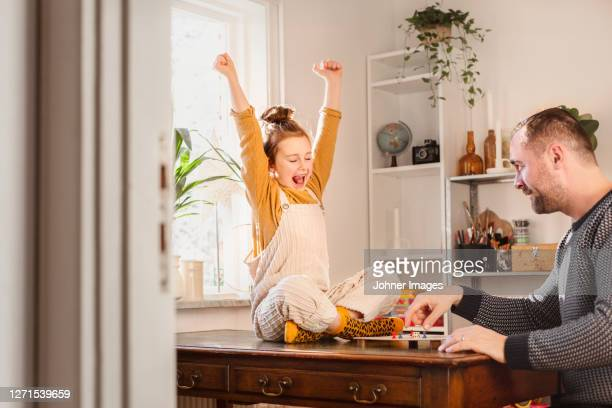 father and daughter playing board game - stretching stock pictures, royalty-free photos & images