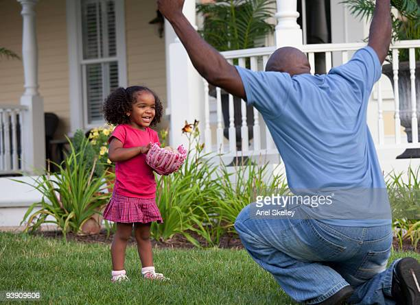 Father and daughter playing catch in front yard