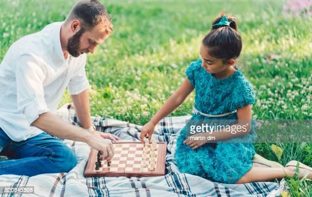 Vader en dochter spelen schaak in het park