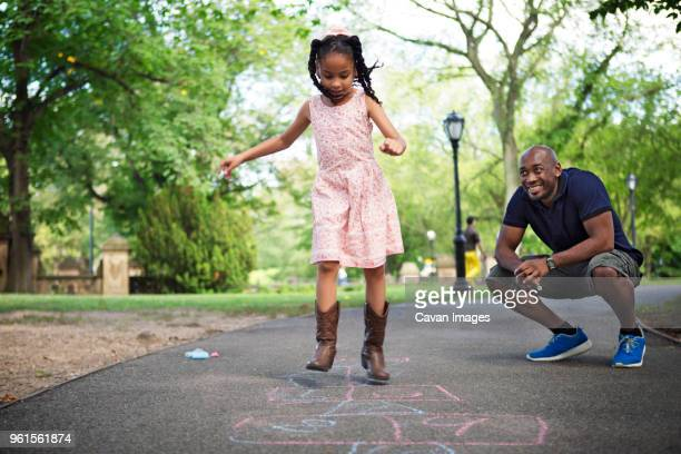 Father and daughter playing hopscotch on road at park