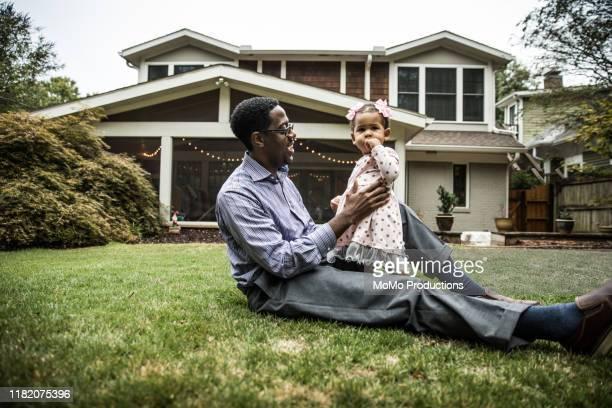 father and daughter (18 months) playing in backyard - voor of achtertuin stockfoto's en -beelden