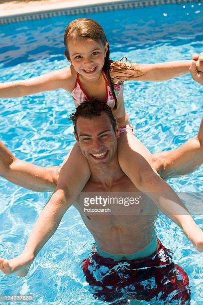 Father and daughter playing in pool