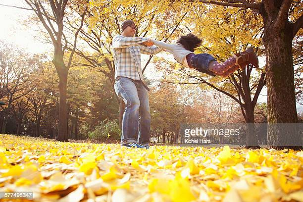 father and daughter playing in the park in autumn