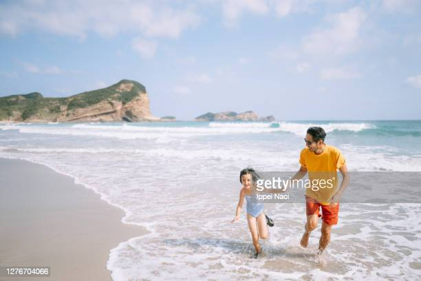 father and daughter playing in waves on beach, japan - 鹿児島県 ストックフォトと画像
