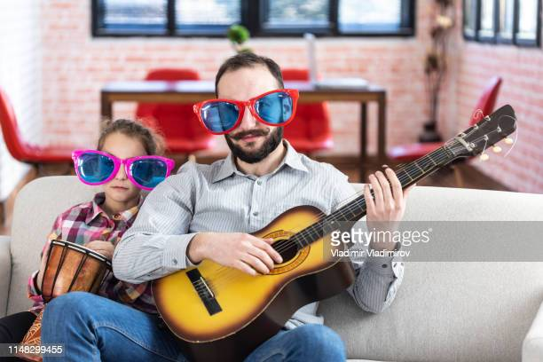 father and daughter playing instruments at home, funny sunglasses - family with one child stock pictures, royalty-free photos & images