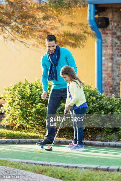 Father and daughter playing miniature golf