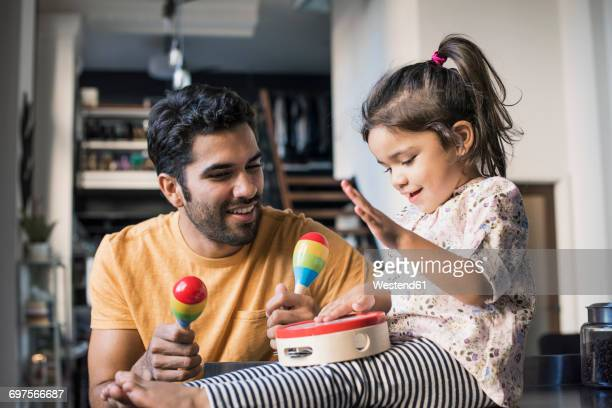 father and daughter playing music in kitchen - tambourine stock pictures, royalty-free photos & images