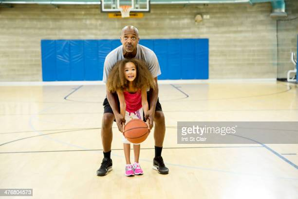 Father and daughter playing on basketball court